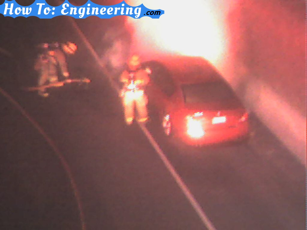 car on fire being put out by firemen